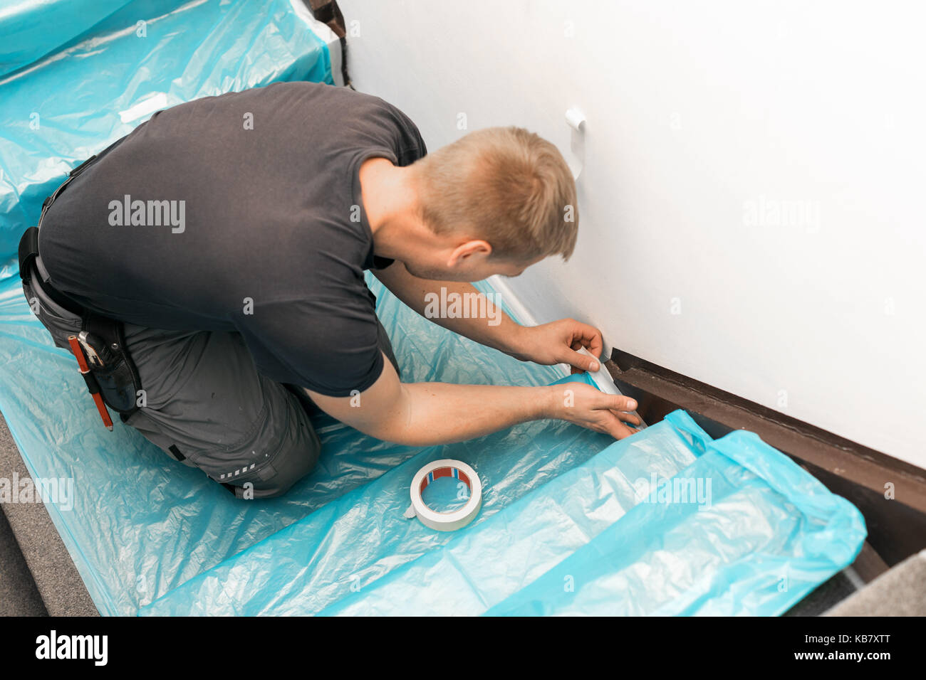 worker covering stairs carpet with masking film before home improvement works Stock Photo