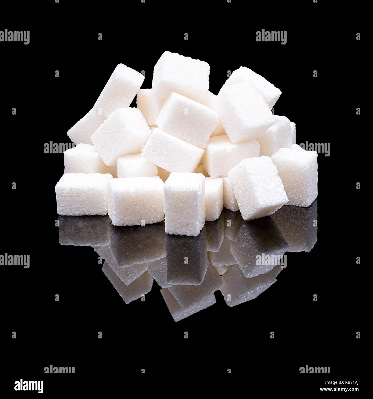 Cubes of white sugar from sugar beet with a real reflection on a black glossy background - Stock Image