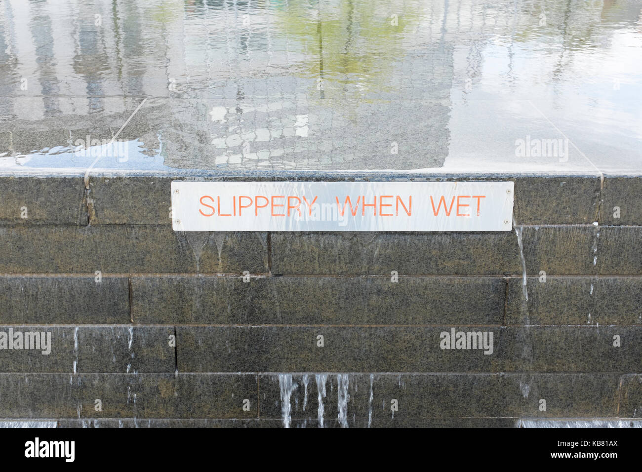 Sign on a water feature in Old Market Square, Nottingham saying slippery when wet - Stock Image