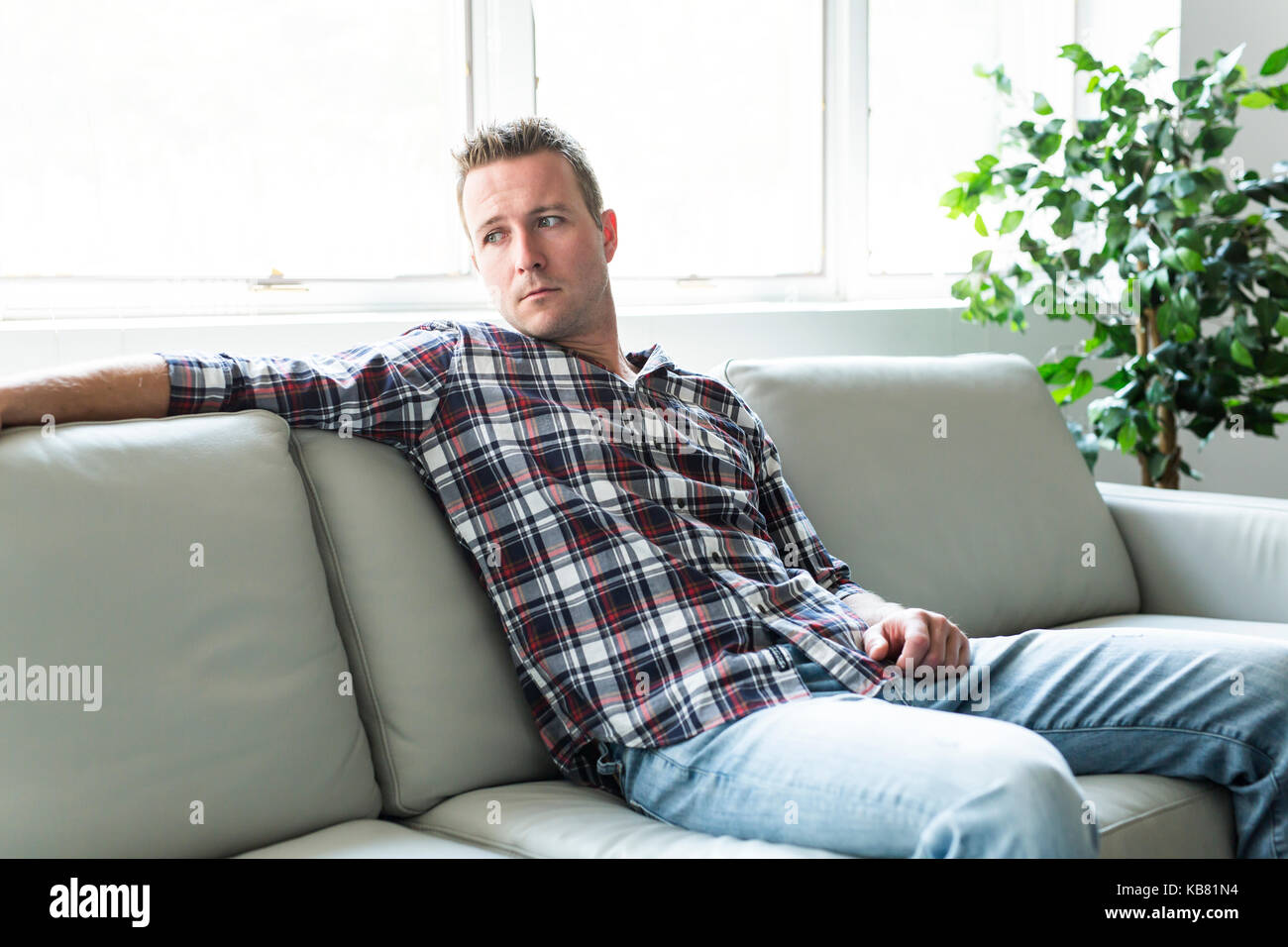 Depressed man thinking on the sofa alone at home - Stock Image