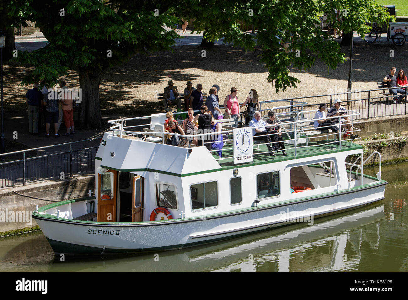Tourists are pictured sitting in a sightseeing river cruise boat as it prepares to depart and travel along the river - Stock Image