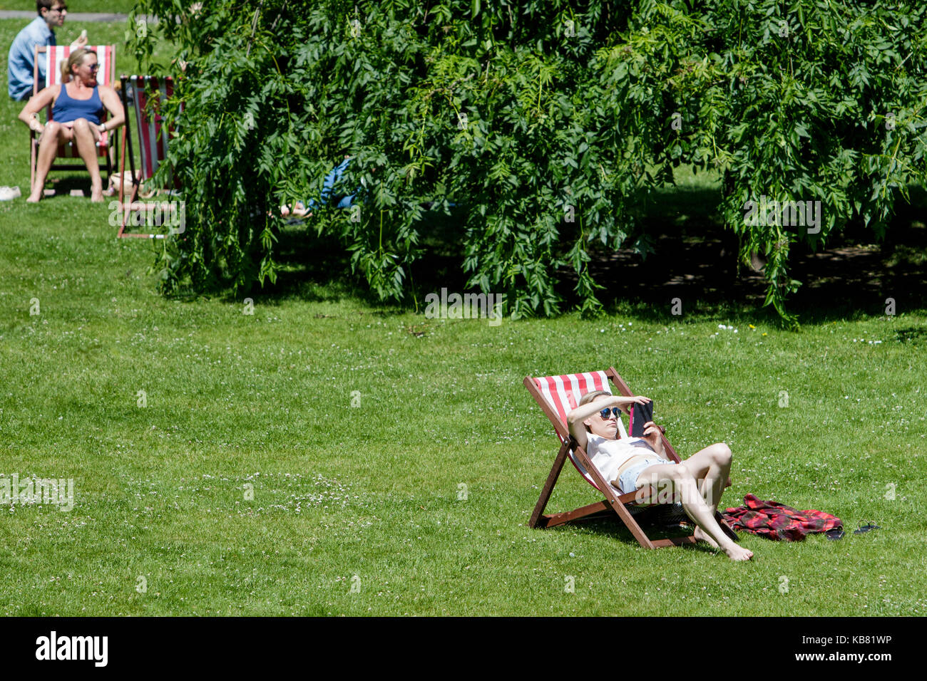 A woman reading a book and enjoying the warm sunshine and hot weather is pictured sitting in a deckchair in a public - Stock Image