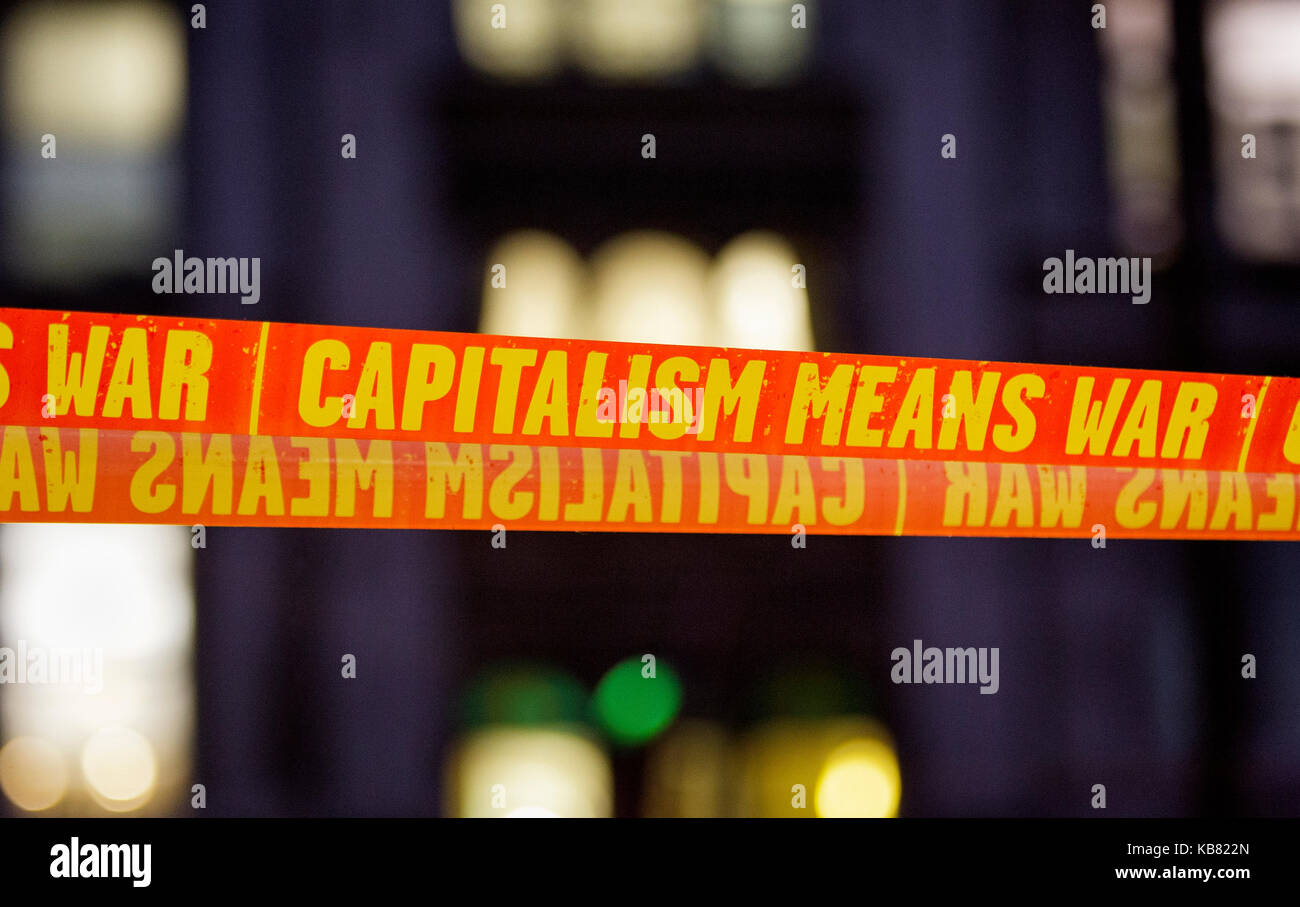 Tape bearing anti-capitalist capitalism slogans are photographed in Parliament square during a demonstration protest - Stock Image