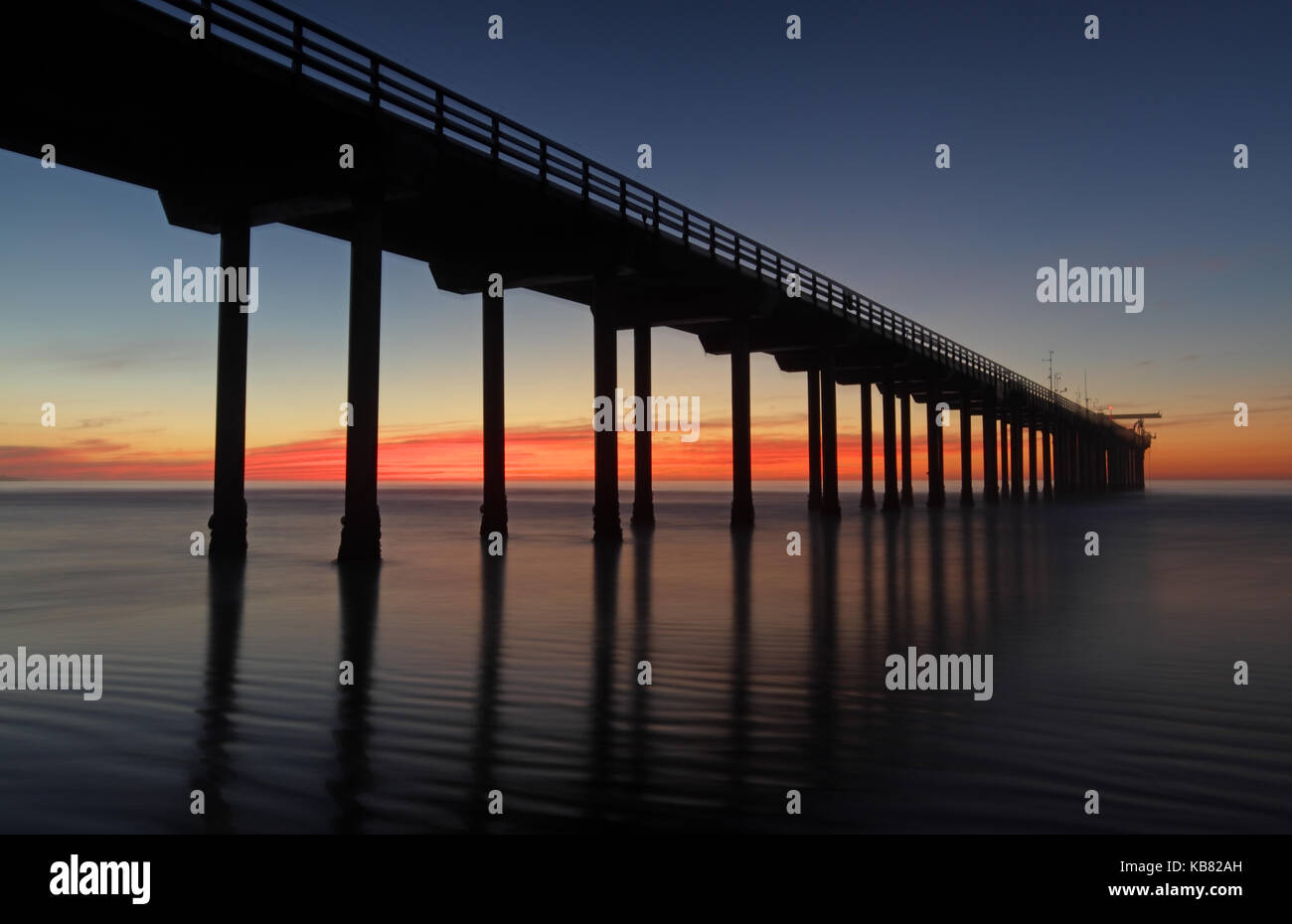 A horizontal seascape of the Scripps Pier in La Jolla, California at one of San Diego's beaches with a colorful - Stock Image
