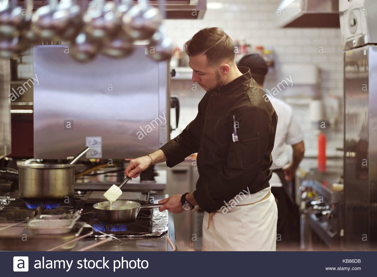 Food concept. A young cook stands in the kitchen and prepares a dish. - Stock Image