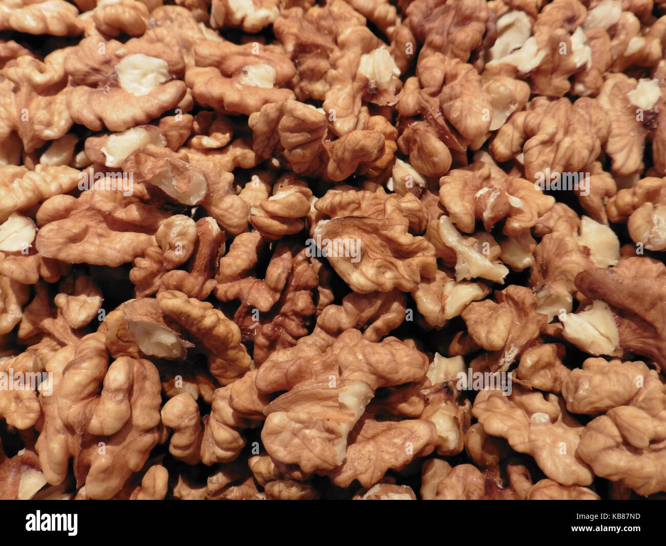 Background of a heap of freshly cracked walnut cores Stock Photo