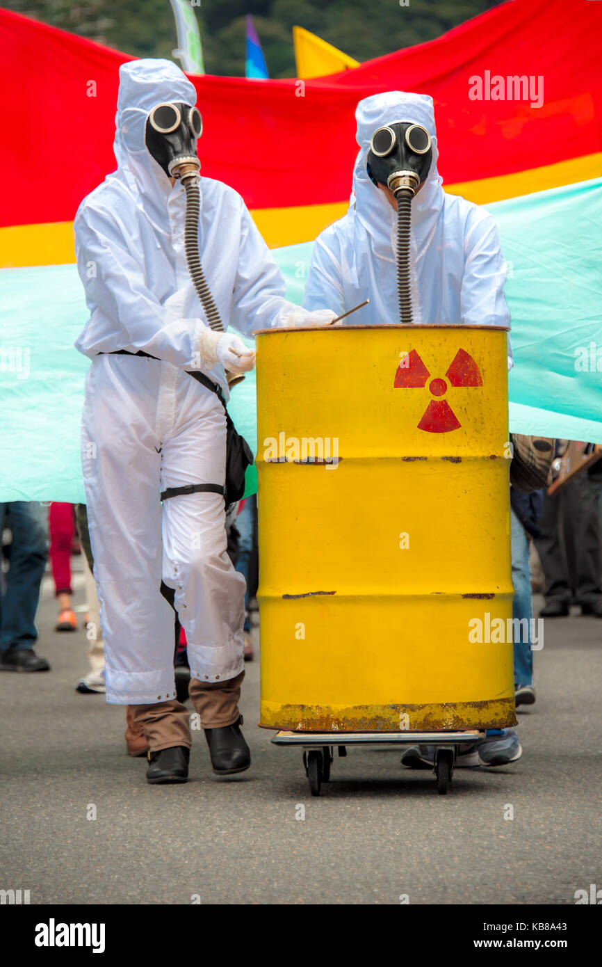 Two men in bio-hazard suits and gas masks. Two men in biohazard suits and gas masks standing behind a rusty tank - Stock Image