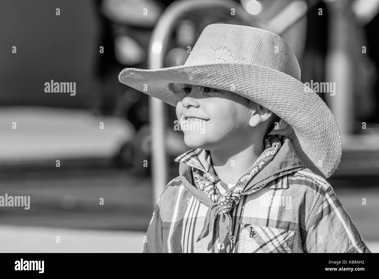 13230dbe4836b Young boy dressed in western attire smiles during portrait shoot - Stock  Image