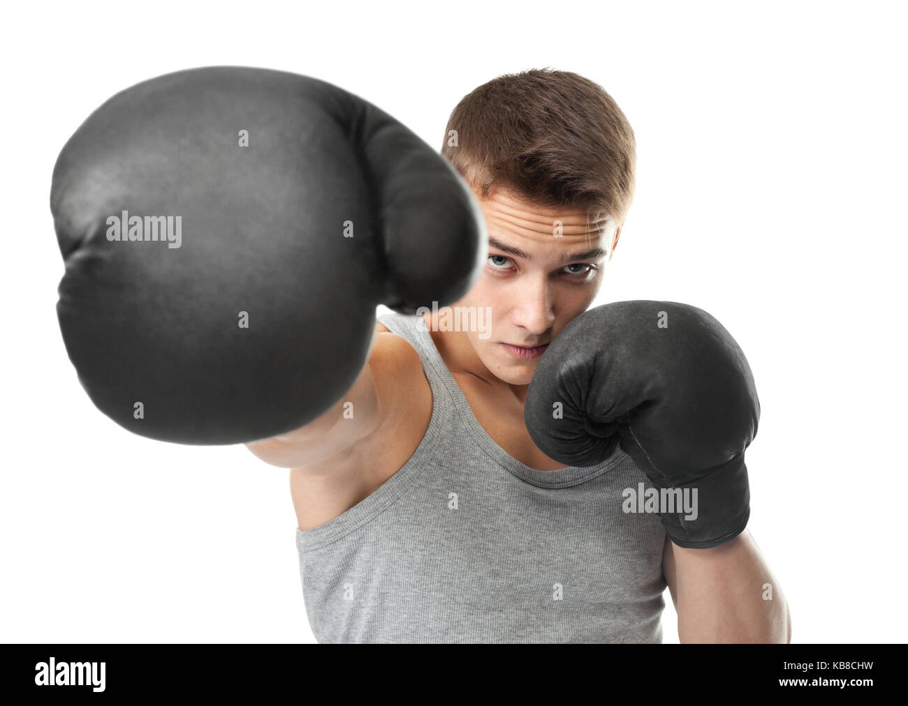 Portrait of young boxer throwing a punch at the camera isolated on white background Stock Photo