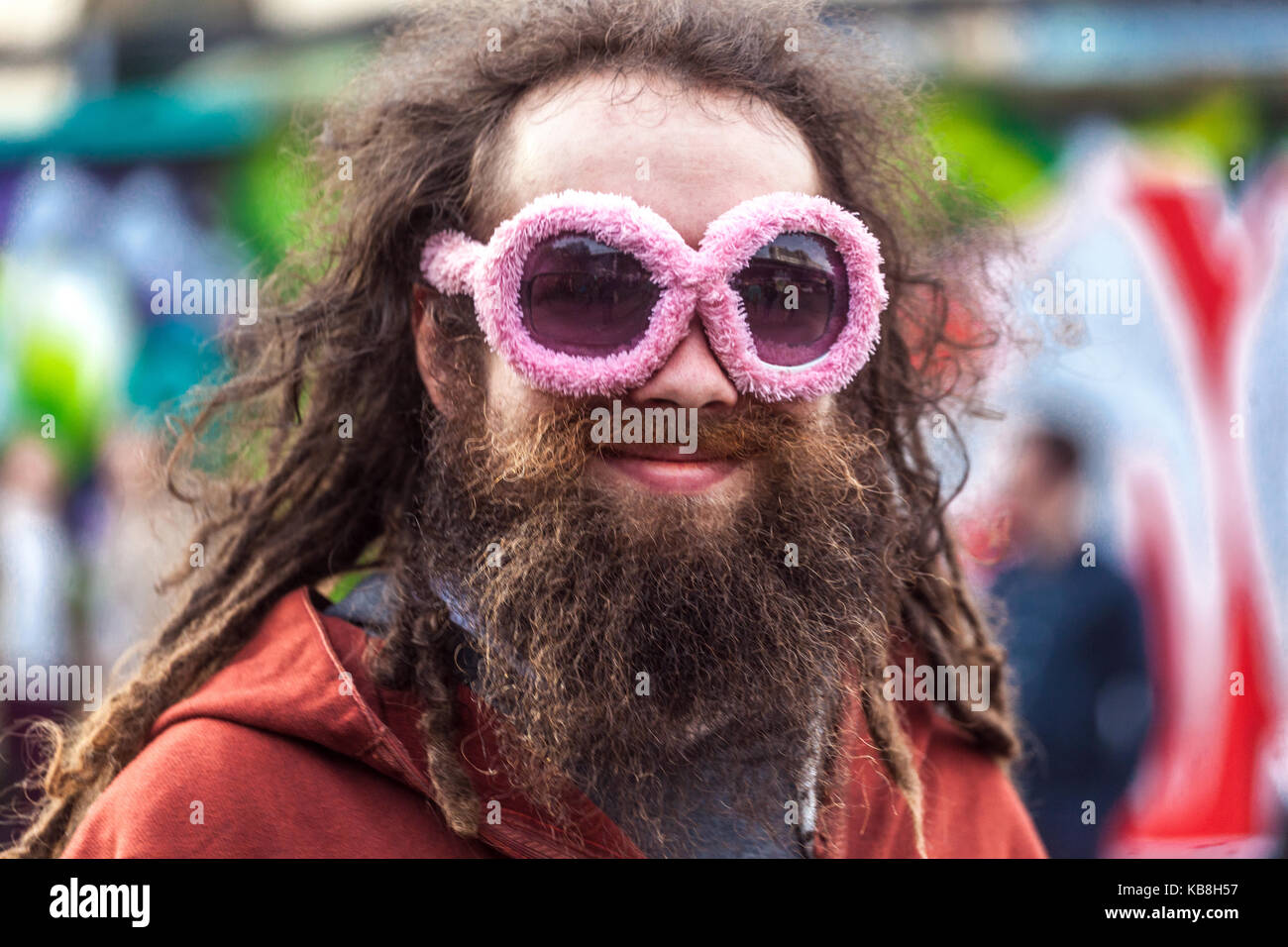 Portrait of a young bearded hipster with pink glasses - Stock Image