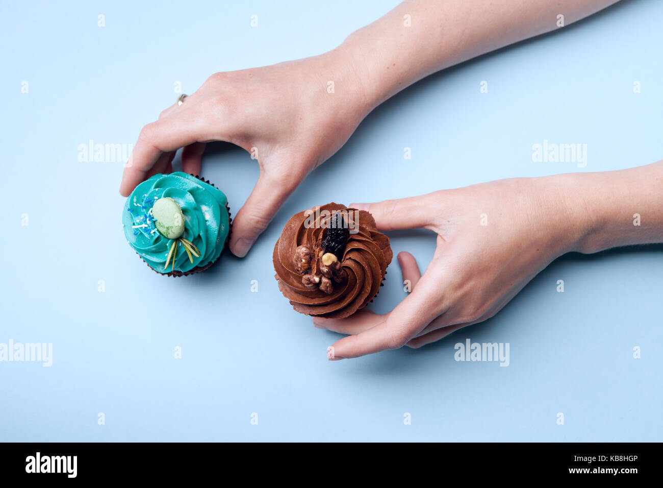 Two delicious cupcakes with cream in hands on a blue background - Stock Image