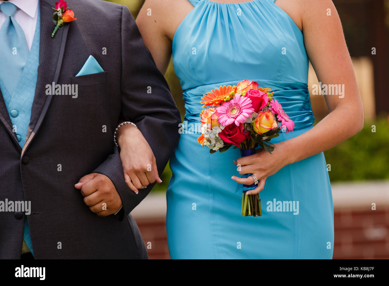 An orange, pink, red, yellow bouquet being held by a bridesmaid wearing a blue dress walking down the aisle with Stock Photo