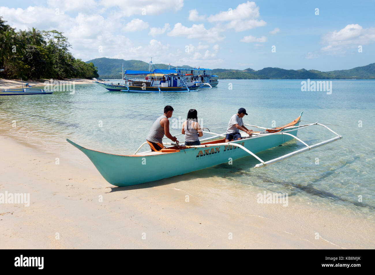 Palawan Philippines - local people pushing a boat out, El Nido, Palawan, Philippines Asia - Stock Image