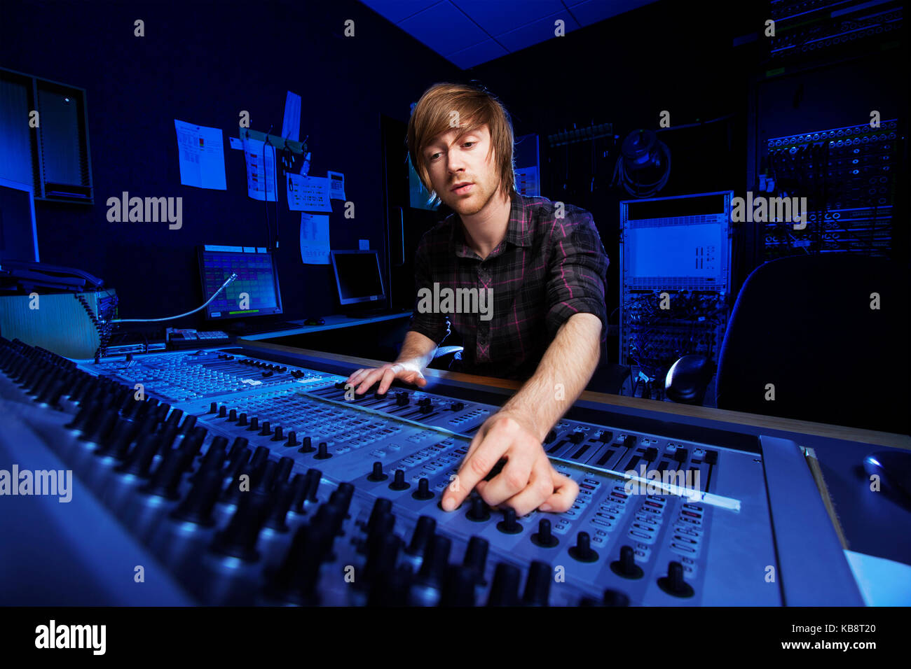 Man using a sound mixing desk in a recording studio - Stock Image
