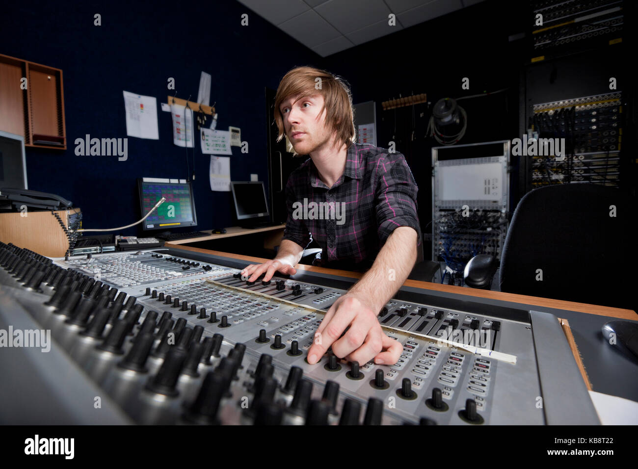 Man using a sound mixing desk in a recording studio. - Stock Image