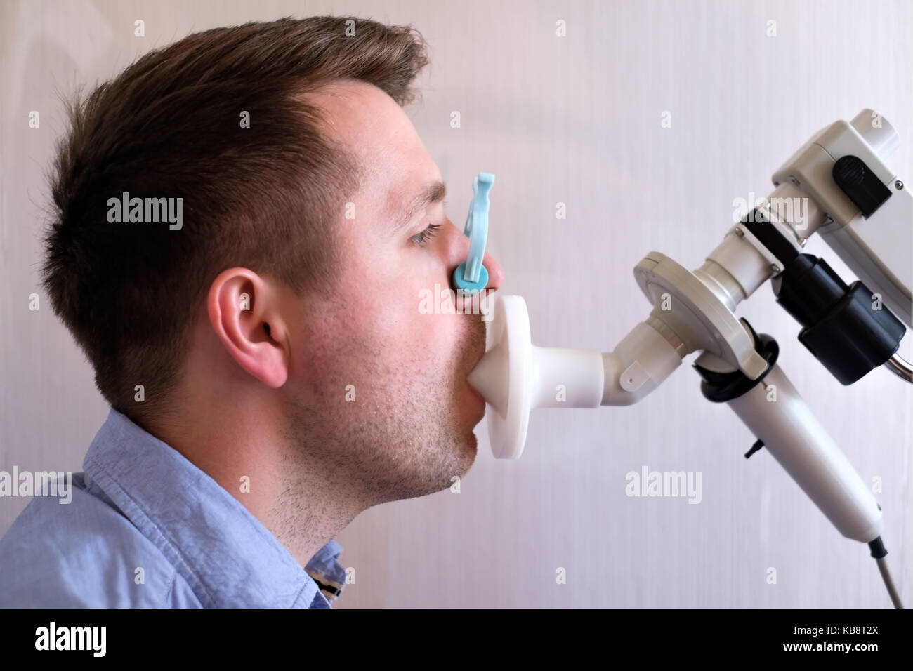 Young man testing breathing function by spirometry - Stock Image