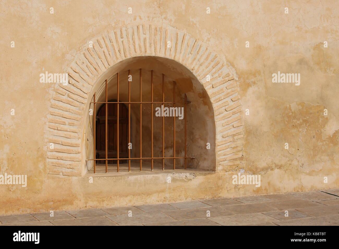Vergittertes Fester in einer beigen Wand - Latticed fixed in a beige wall - Stock Image