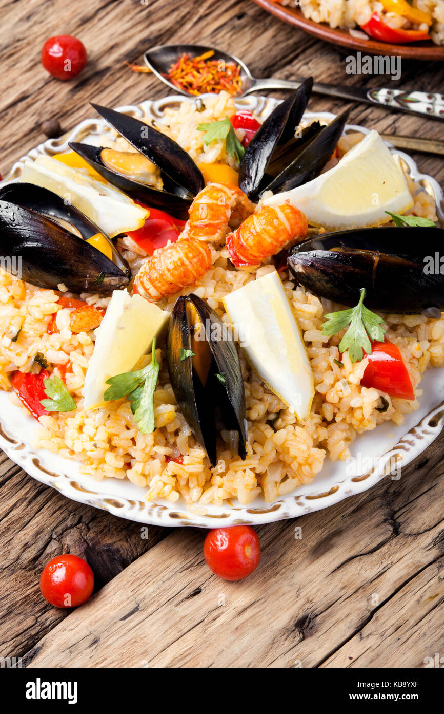 Traditional vegetable paella with seafood on wooden background Stock Photo