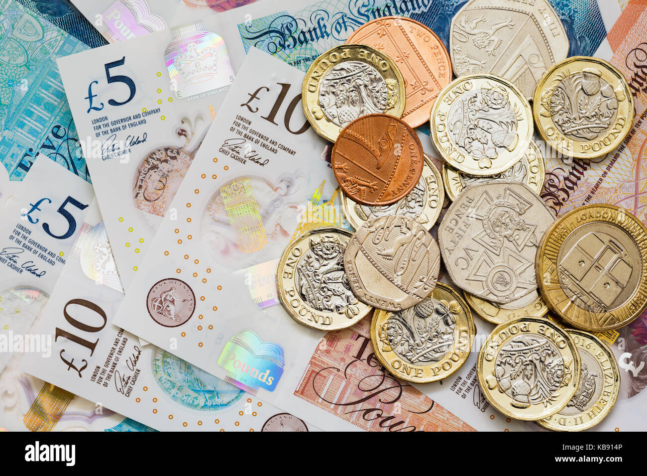British UK money sterling £10 and £5 notes GBP and a pile of new issue pounds one pound coins cash. Saving - Stock Image