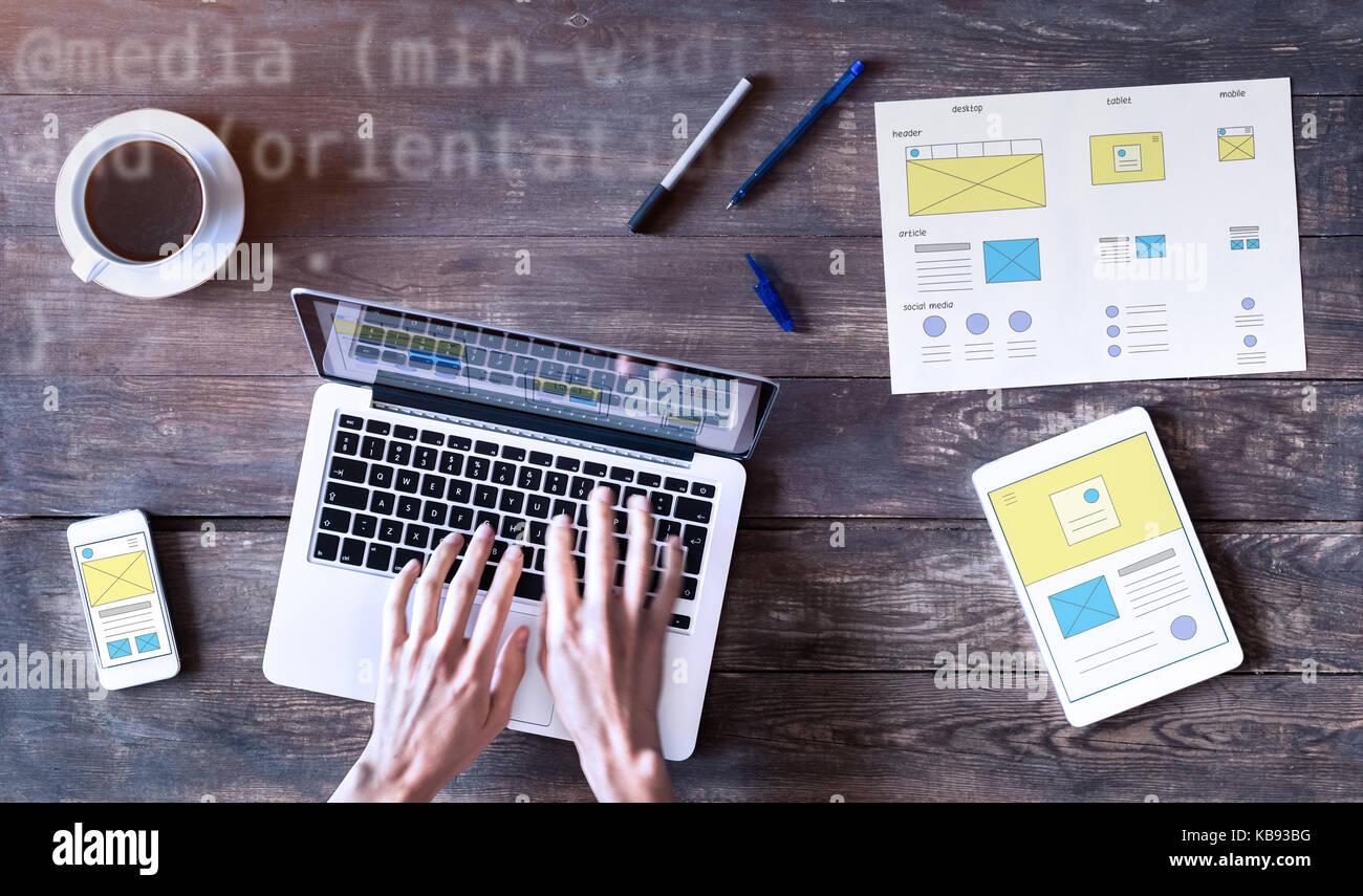 Webdesigner sketching responsive website wireframe mockup with laptop, smartphone and digital tablet computer on - Stock Image