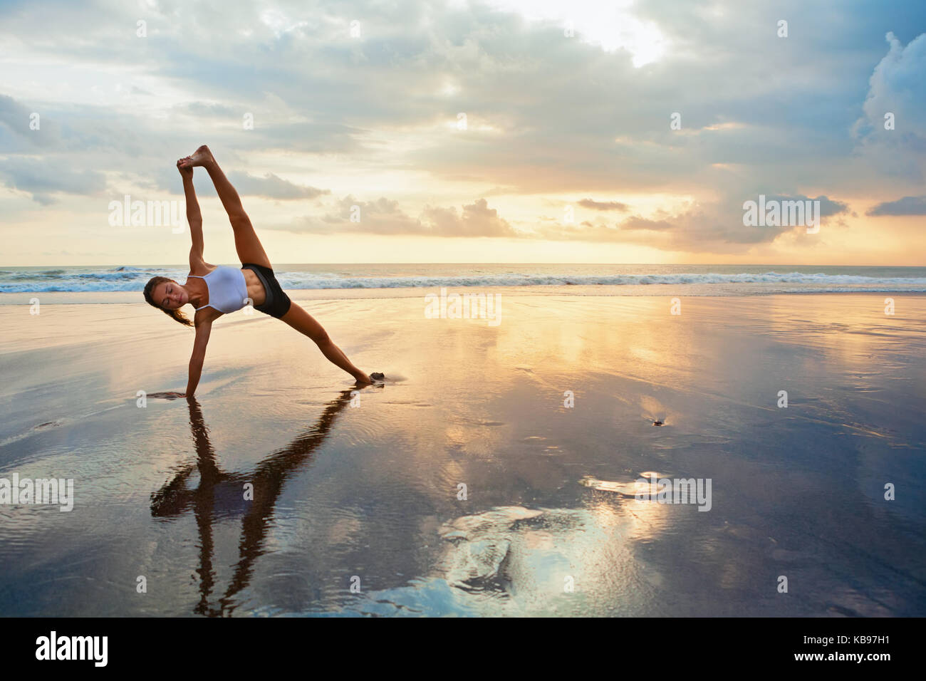 Meditation on sunset sky background. Young active woman in yoga pose on sea beach, stretching to keep fit, health. - Stock Image