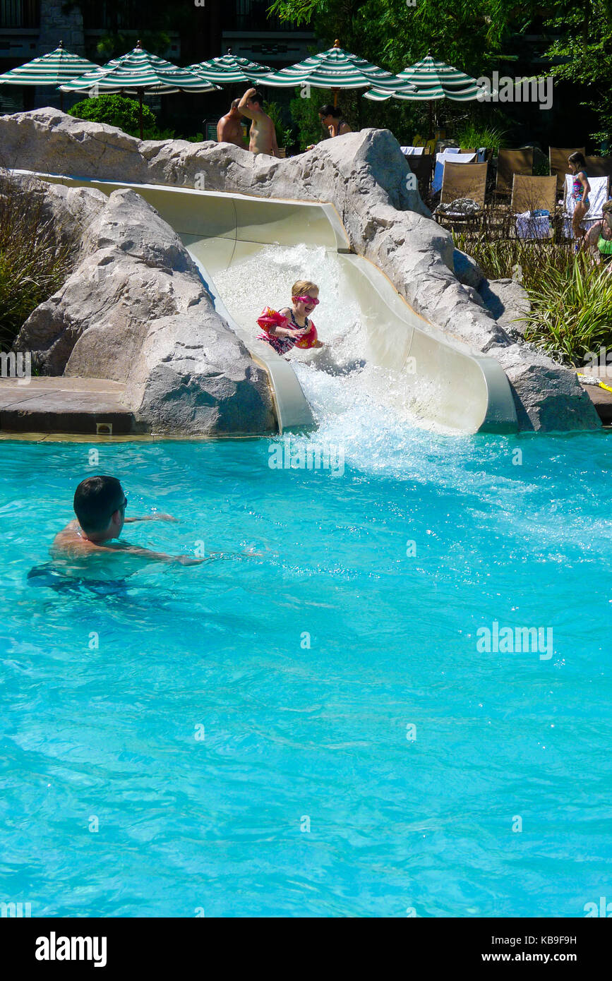 Child In Armbands Coming Down A Fast Slide Into A Swimming Pool   Stock  Image