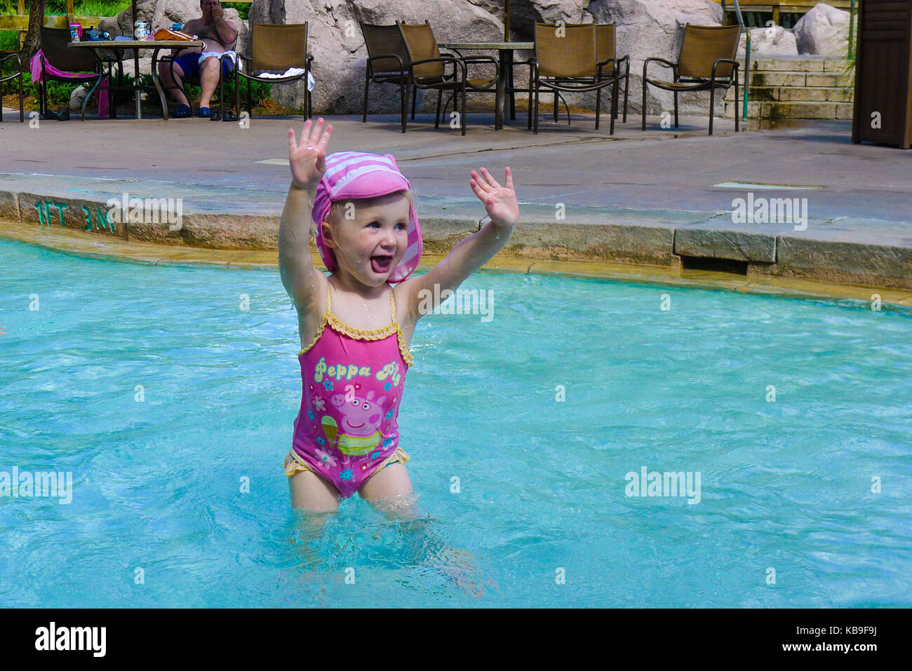 3d1fcd802a Child in a swim hat and peppa pig swimsuit standing in a swimming pool with  hands