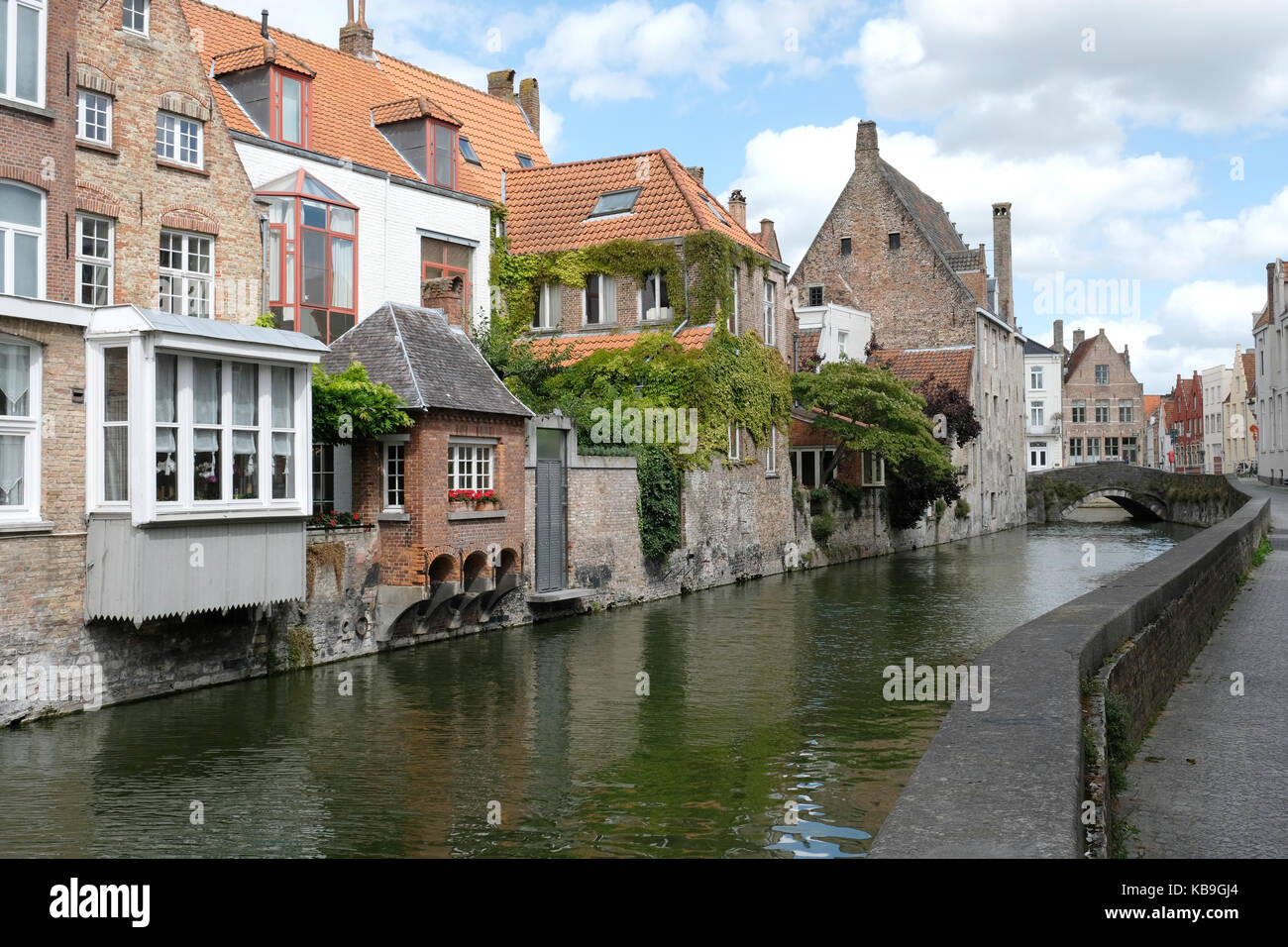 Typical canal scene in Bruges / Brugge, Belgium showing medieval buildings overlooking the water - Stock Image