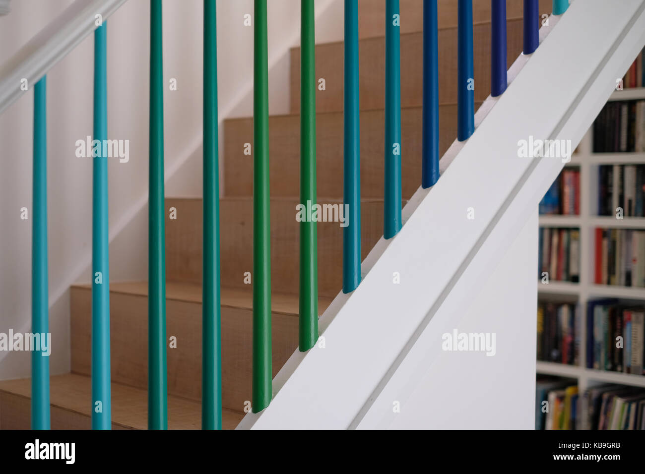 Residential Wooden Staircase With Spindles Painted In Green And Blue Ombre  Colours, And Book Shelves