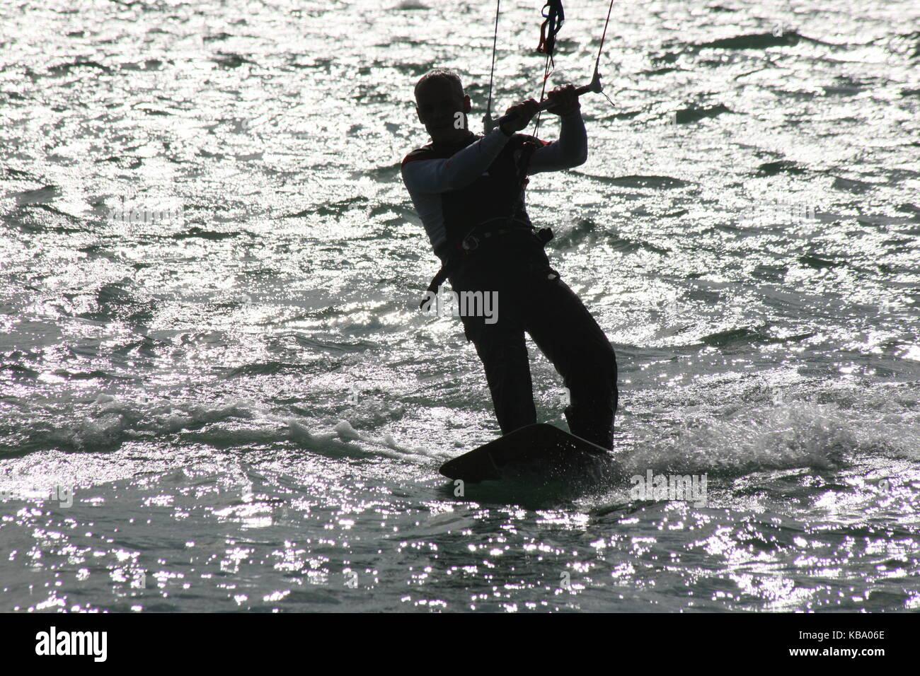 Surfer on surfboard with sail --- Kite Surfer auf Surfboard  im Gegenlicht - Stock Image