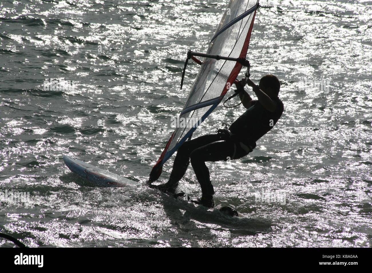 Surfer on surfboard with sail --- Surfer auf Surfboard mit Segel - Stock Image