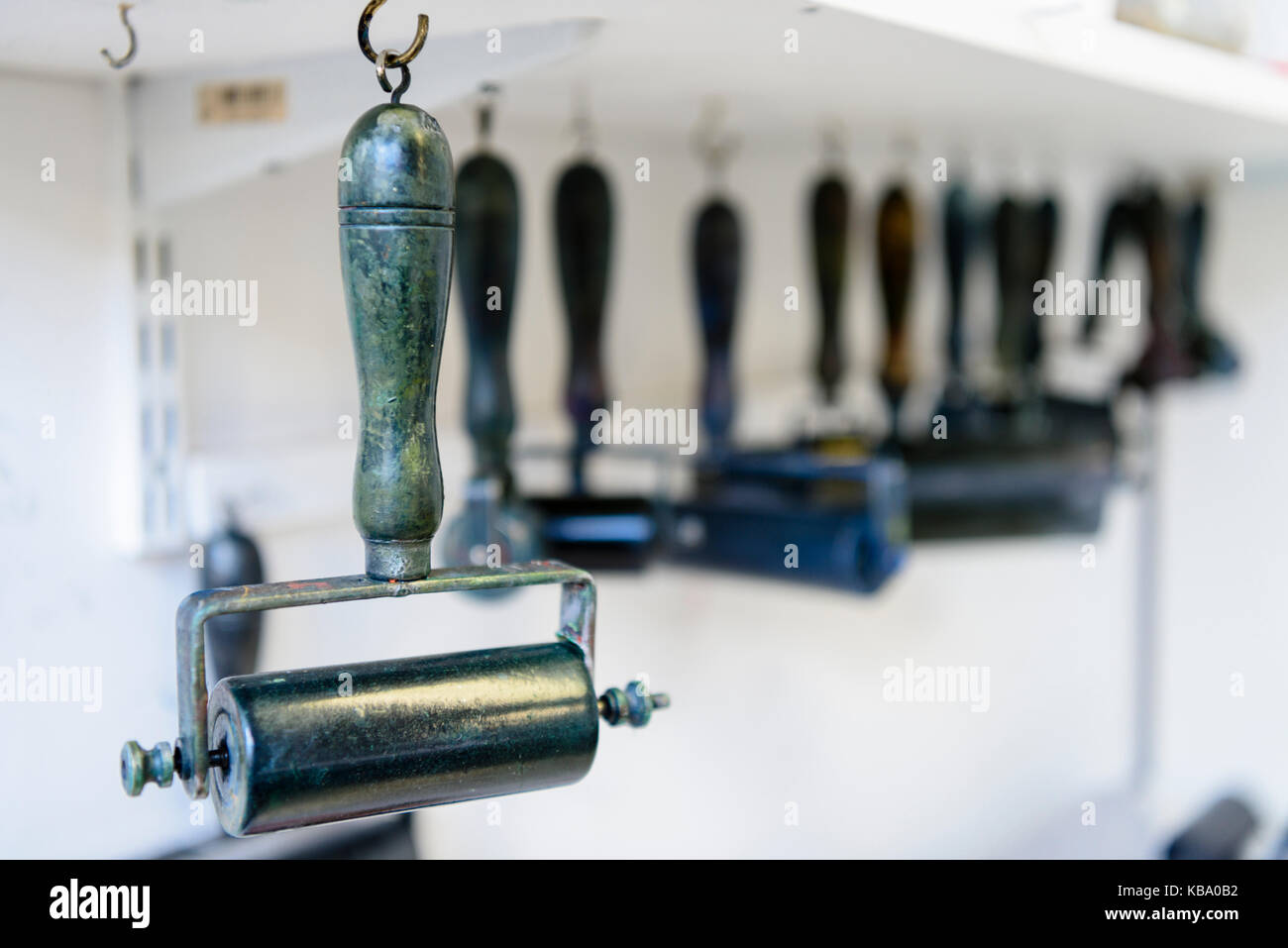 Ink rollers hanging in a printer's workshop. - Stock Image
