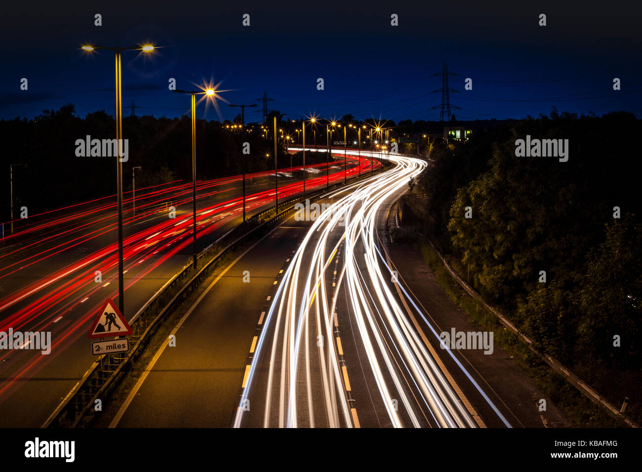 Taken late evening over motorway bridge. Motion blur of headlights and taillights - Stock Image