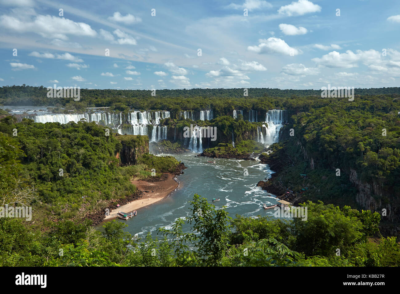 Iguazu Falls on Argentina side, and tourist boats on Iguazu River, Brazil - Argentina Border, South America - Stock Image