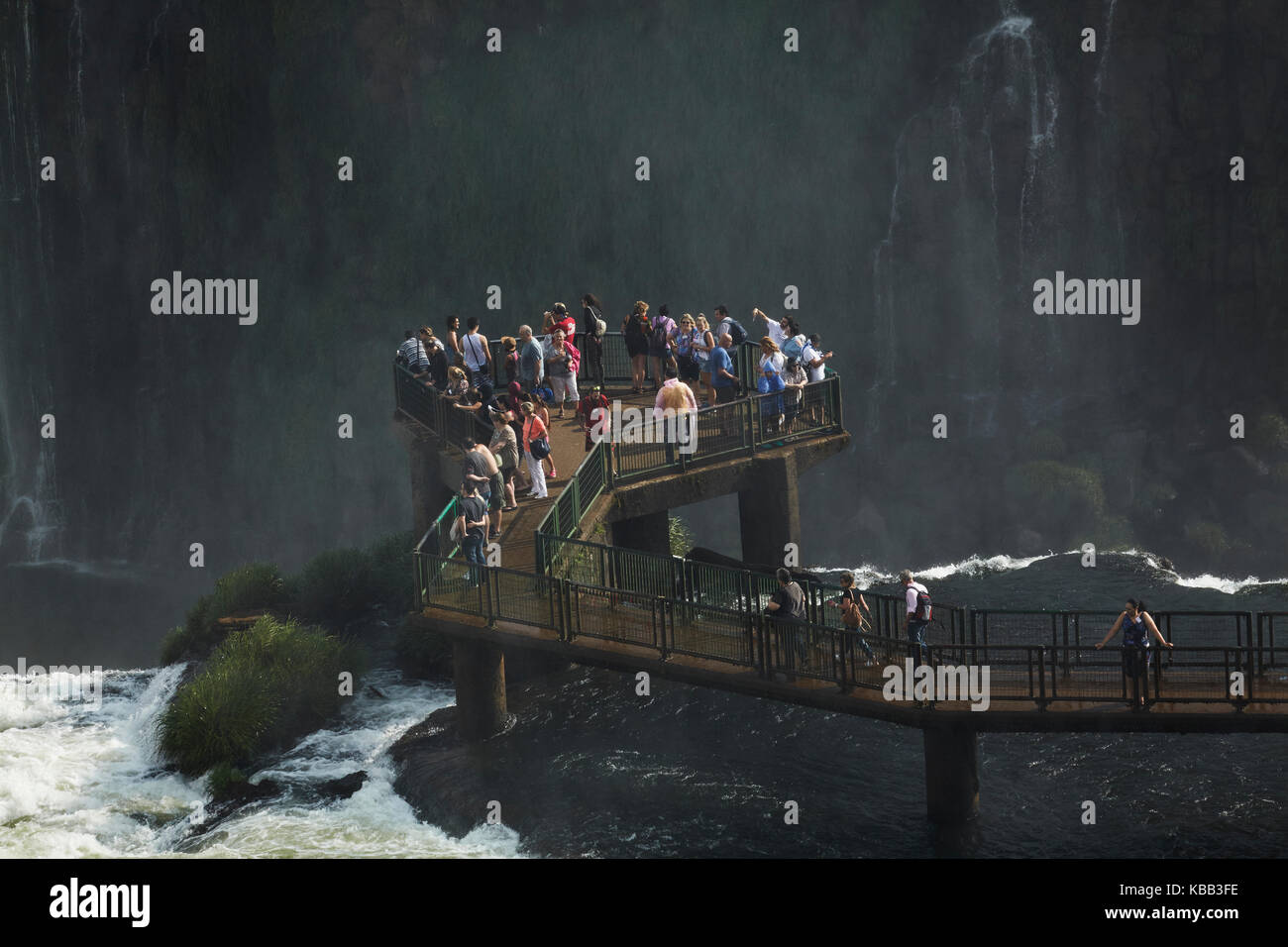Tourists on viewing platform on Brazil side of Iguazu Falls, Brazil - Argentina border, South America - Stock Image