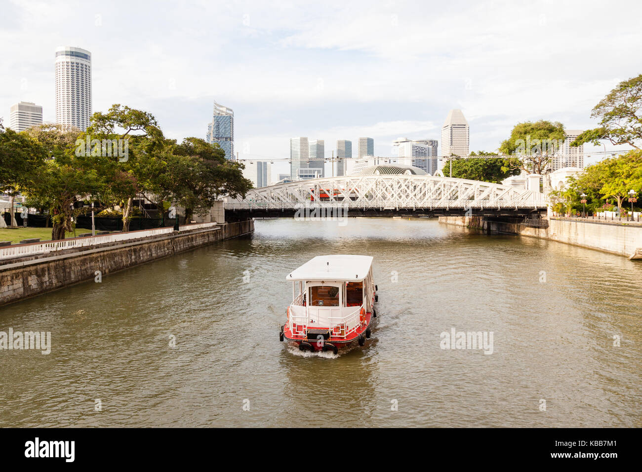 A boat ply the Singapore River on Boat Quay toward Anderson Bridge, with the city's skyline in the background. - Stock Image