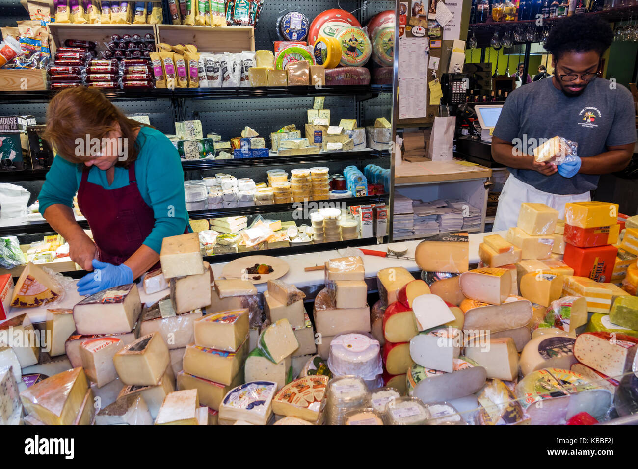 Colonial Williamsburg Virginia The Cheese Shop store shopping inside cheese wedges Black man woman preparing - Stock Image