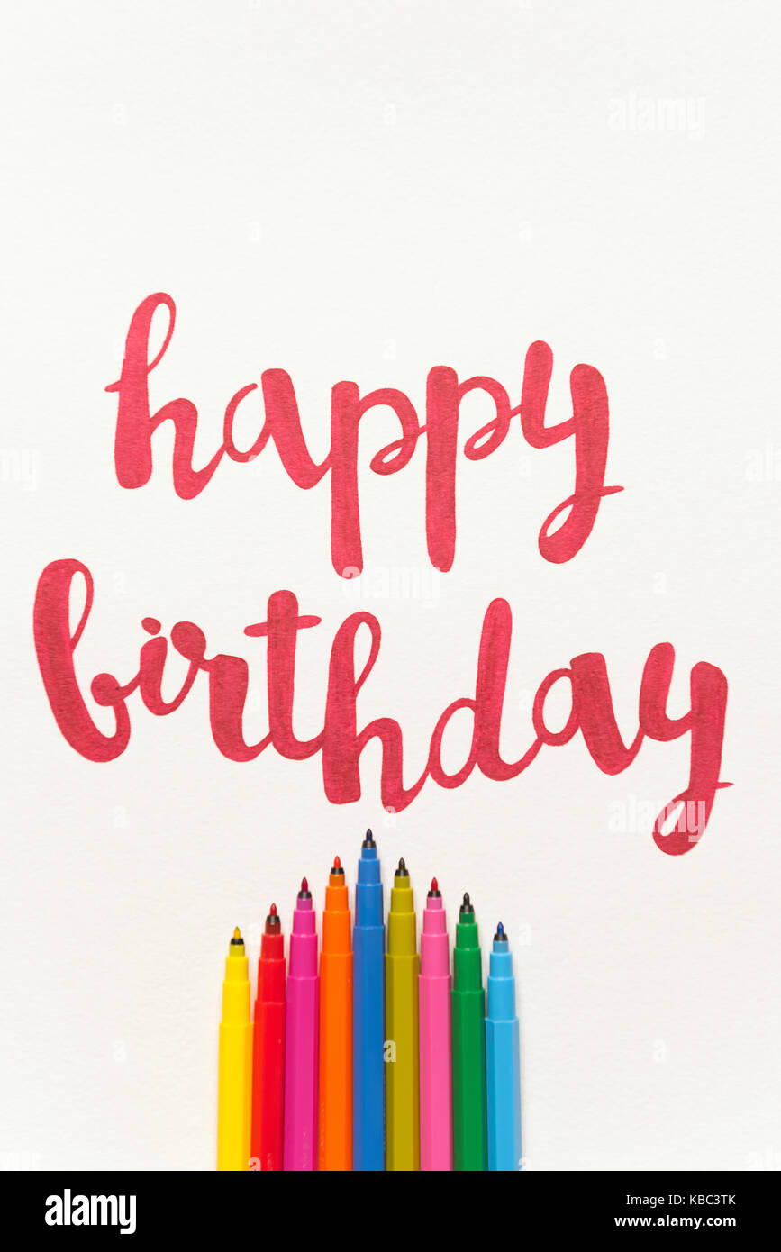 Colourful Phrase Happy Birthday For Greeting Cards And Posters Drawing With Red Marker On White Paper Top View Of Lettering Bunch Mar