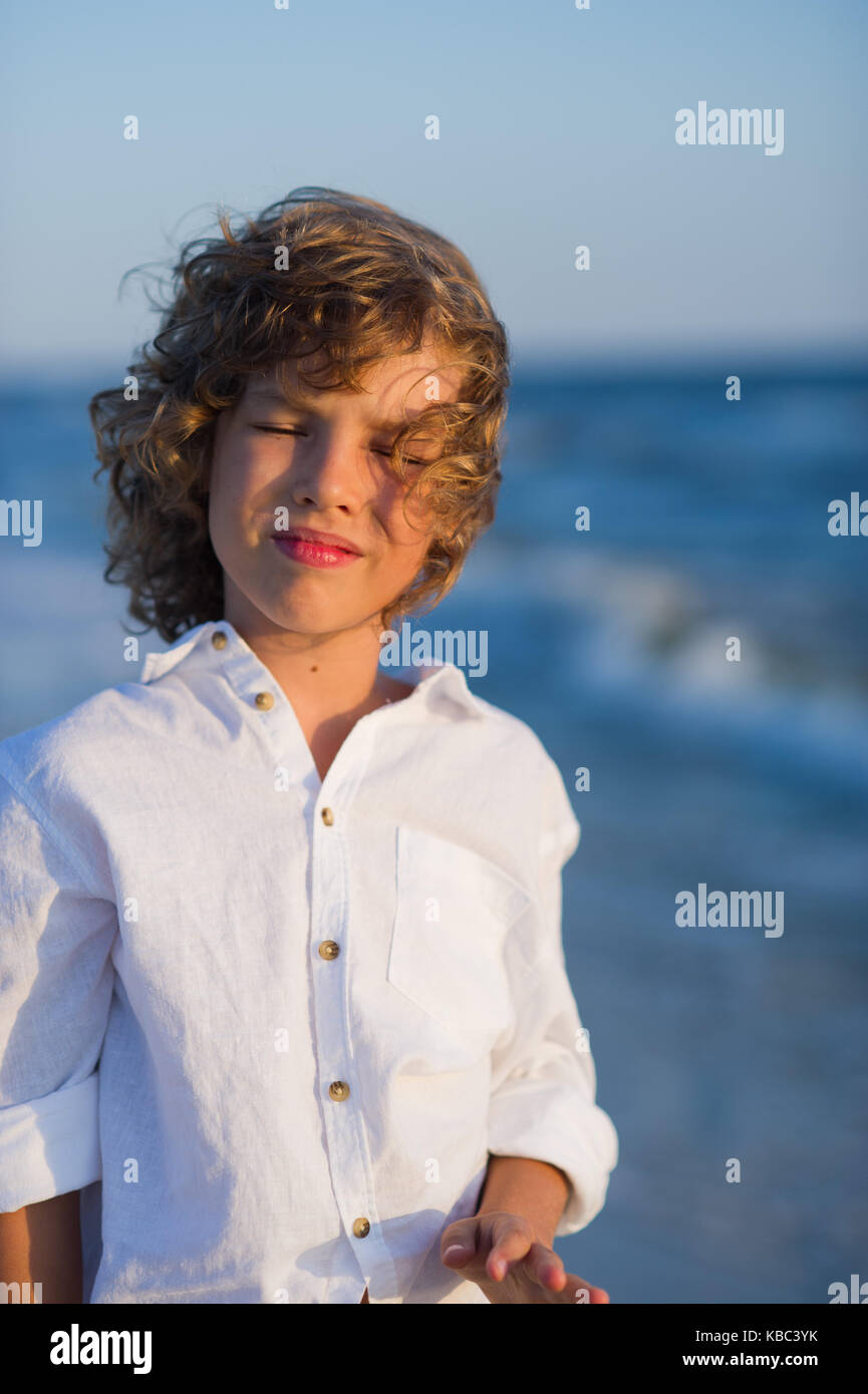 Portrait of boy of 10-11 years against the background of the rough sea. - Stock Image