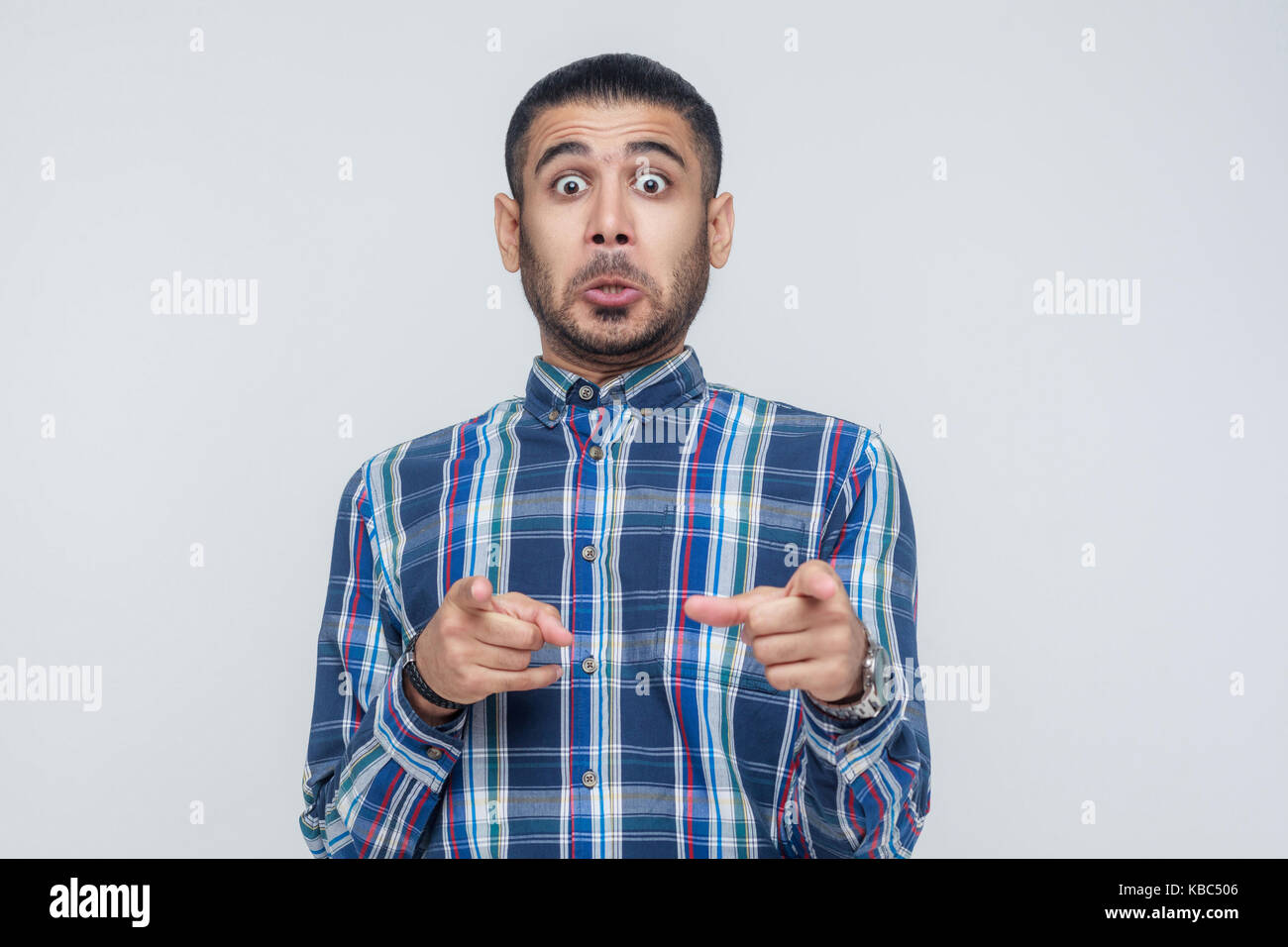 The seriosly man, wearing blue shirt, opening mouths widely, having surprised shocked looks, pointing finger at Stock Photo