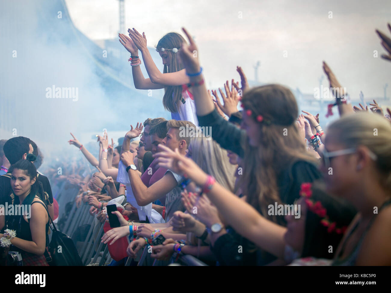 Enthusiastic and energetic music fans go crazy at a concert with the Norwegian DJ and electronic producer Kygo who - Stock Image