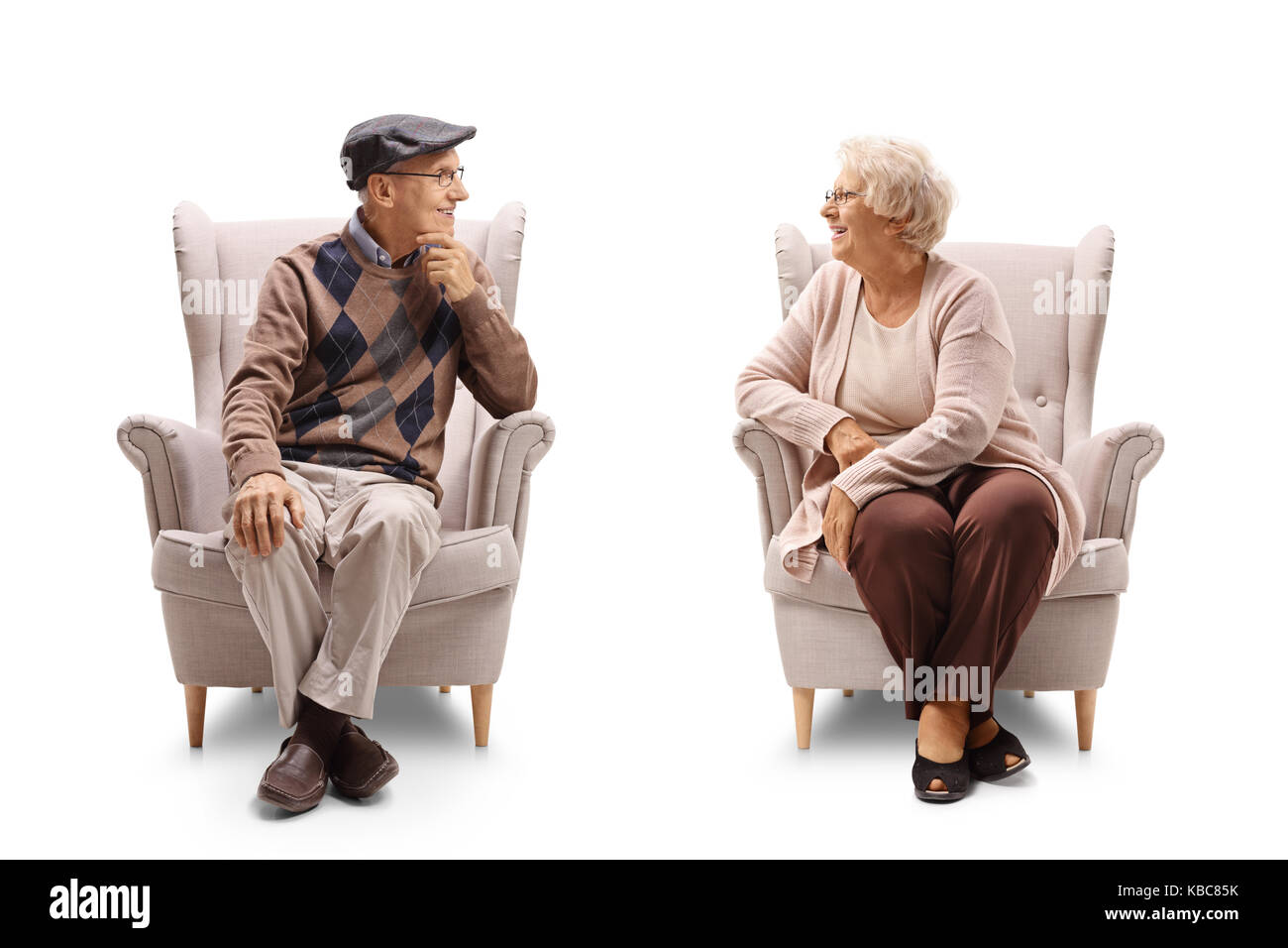 Seniors sitting in armchairs and having a conversation isolated on white background - Stock Image