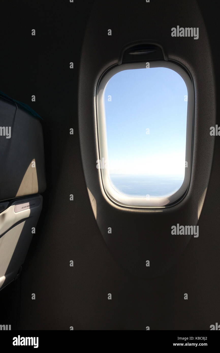 Looking out the airplane window seat into the  blue sky while flying in the air at daytime Stock Photo