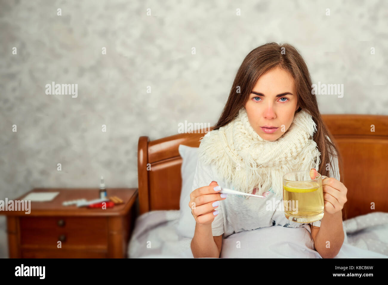 Sick girl with a thermometer on the bed. Virus. Flu. - Stock Image