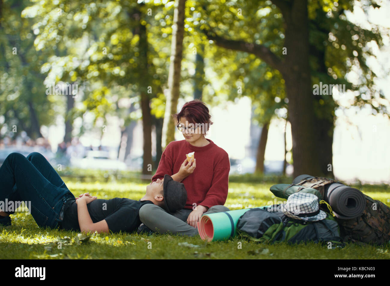 Couple of teenagers tourists with backpacks have rest in the city park - Stock Image