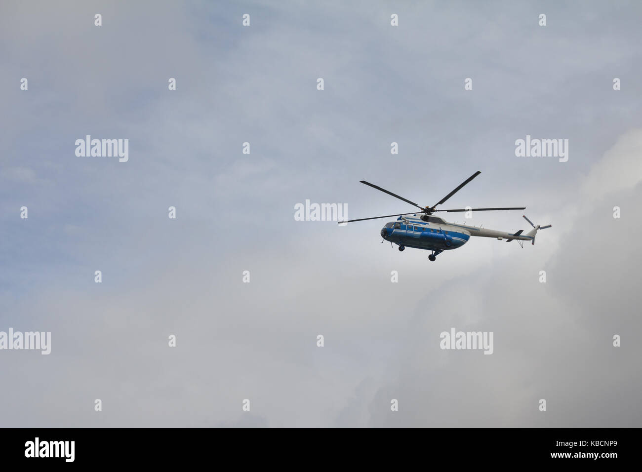 Civil helicopter in cloudy sky - Stock Image