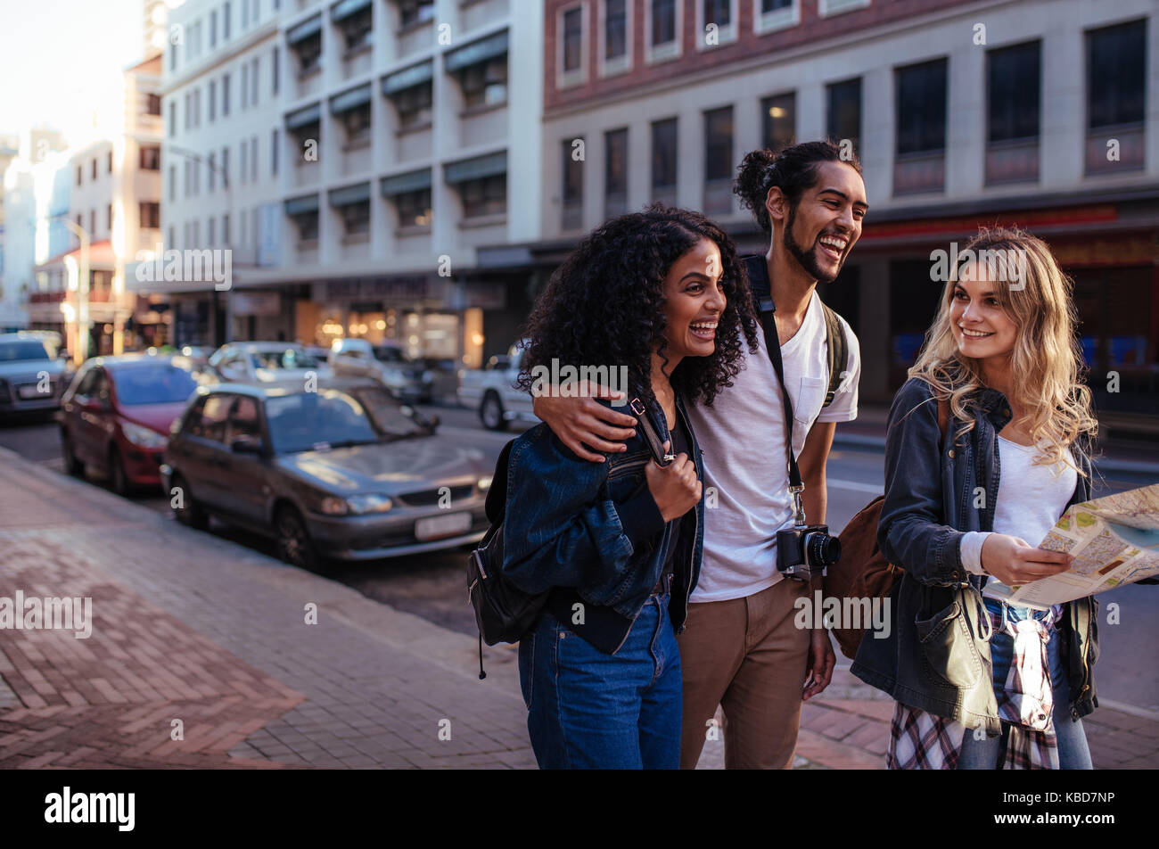 Woman tourist using navigation map to explore the city. Man with two women friends moving around the city. - Stock Image