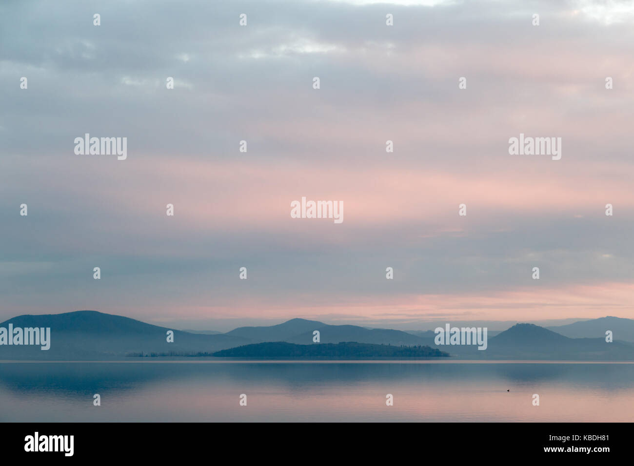 A lake at dusk, with beautiful, warm tones in the sky and water - Stock Image