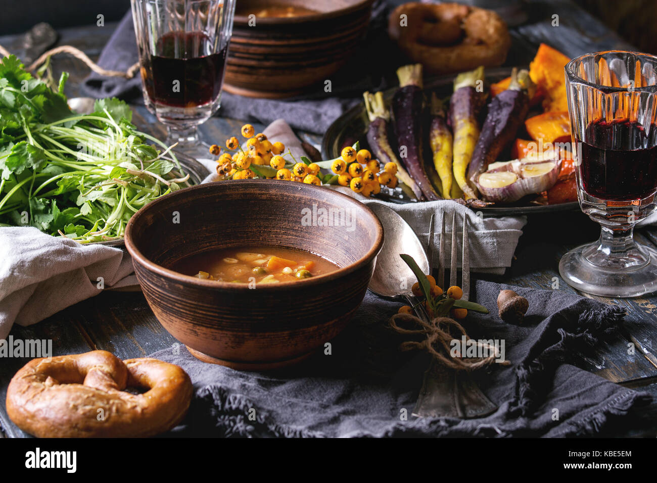 Holiday table decoration setting with bowls of hot soup, baking pumpkin, carrot, garlic, fresh coriander, pretzels Stock Photo