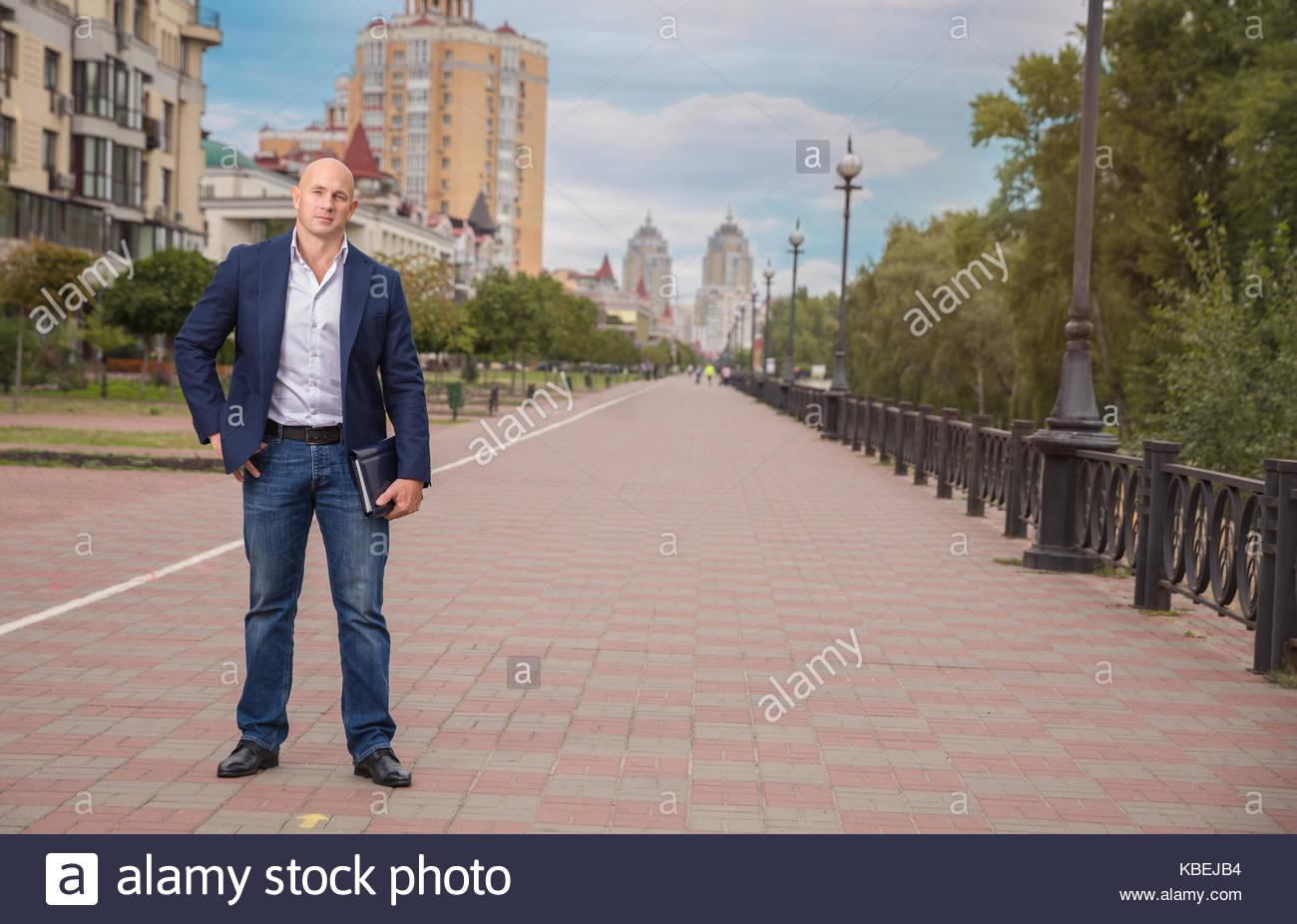 Handsome Bald businessman, realtor staying on sidewalg over houses background - Stock Image